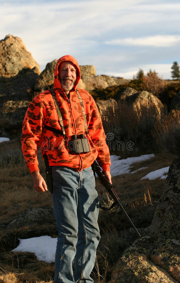 The Great Hunter. A hunter decked out in blaze orange camouflage. Complete with rifle, binoculars, hunting knife and blue jeans. Evening setting sun, very cold stock image
