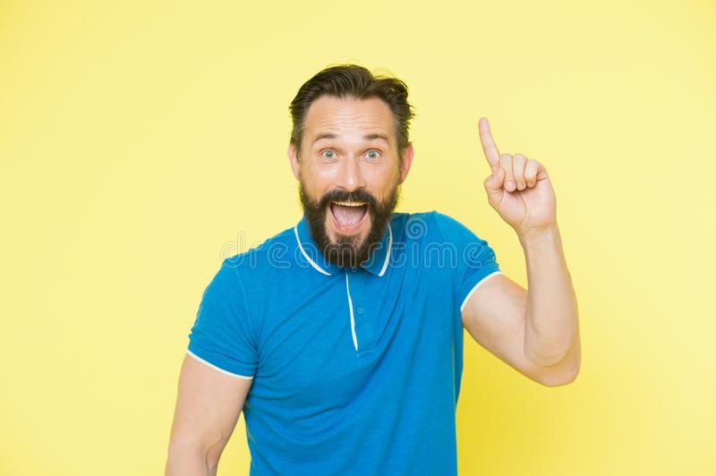 Great idea. Handsome smiling mature man keeping finger raised and looking at camera while standing against yellow stock photos