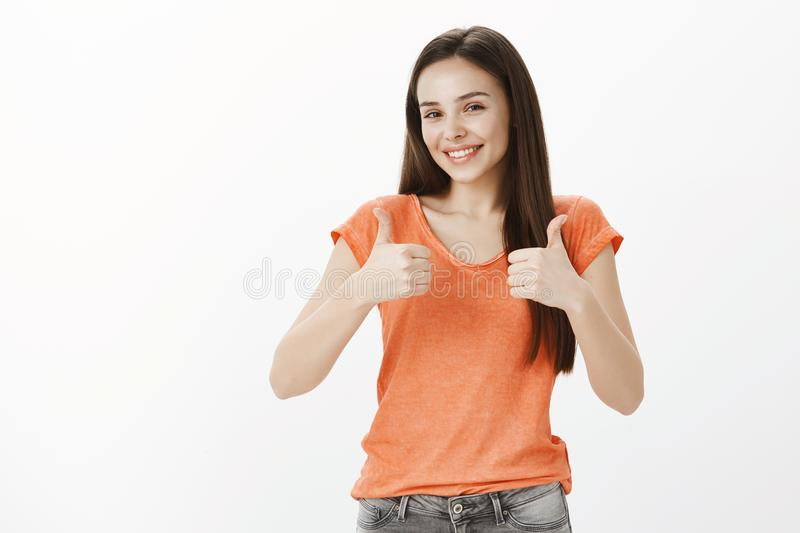 Great idea, like it and adore it. Studio portrait of happy good-looking carefree woman in orange blouse, showing thumbs royalty free stock image