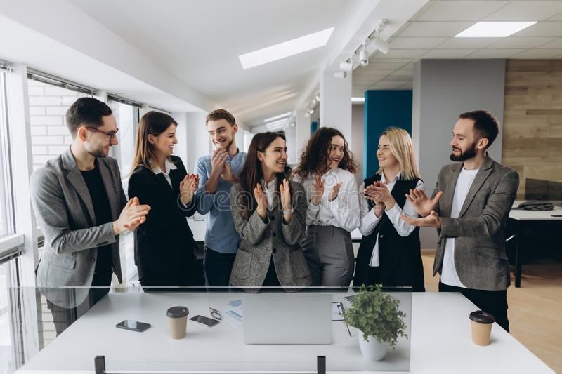 Great job! Successful business team is clapping their hands in modern workstation, celebrating the performance of new product royalty free stock image