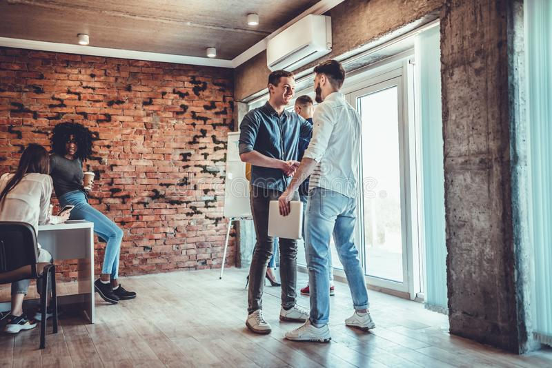Two men handshake to seal deal, cheerful partners greeting each other in loft office stock image