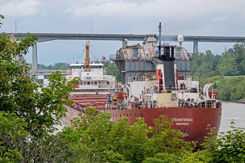 Great Lakes Freighter Going East Toward Lake Ontario. A great lakes freighter heads toward Lake Ontario after transiting the final lock in the Welland Canal. The stock photography