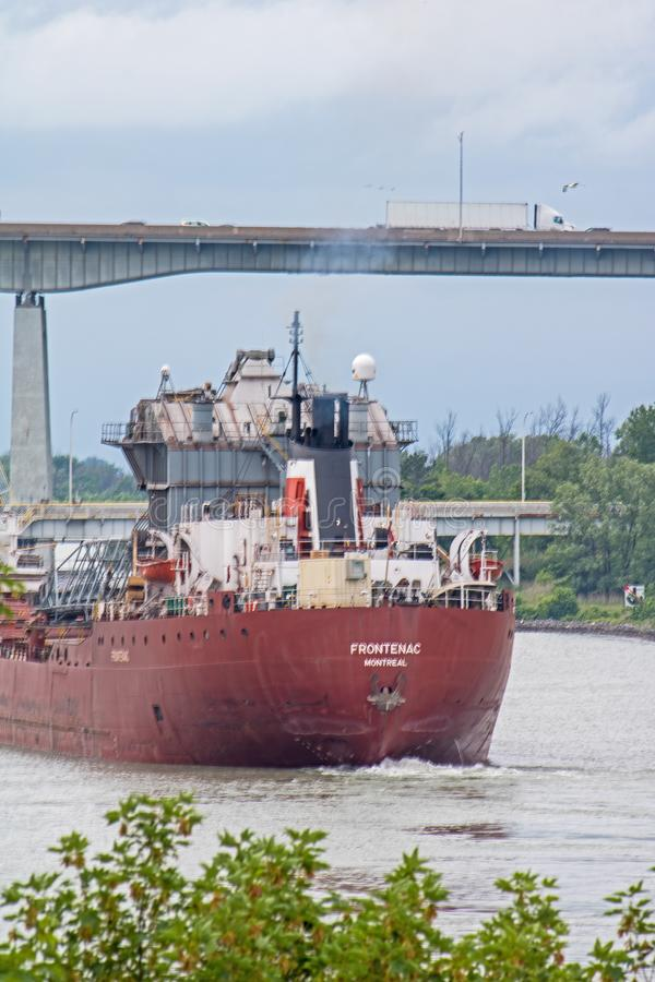 Great Lakes Freighter Leaving The Welland Canal. A great lakes freighter heads toward Lake Ontario after transiting the final lock in the Welland Canal. The ship stock photo