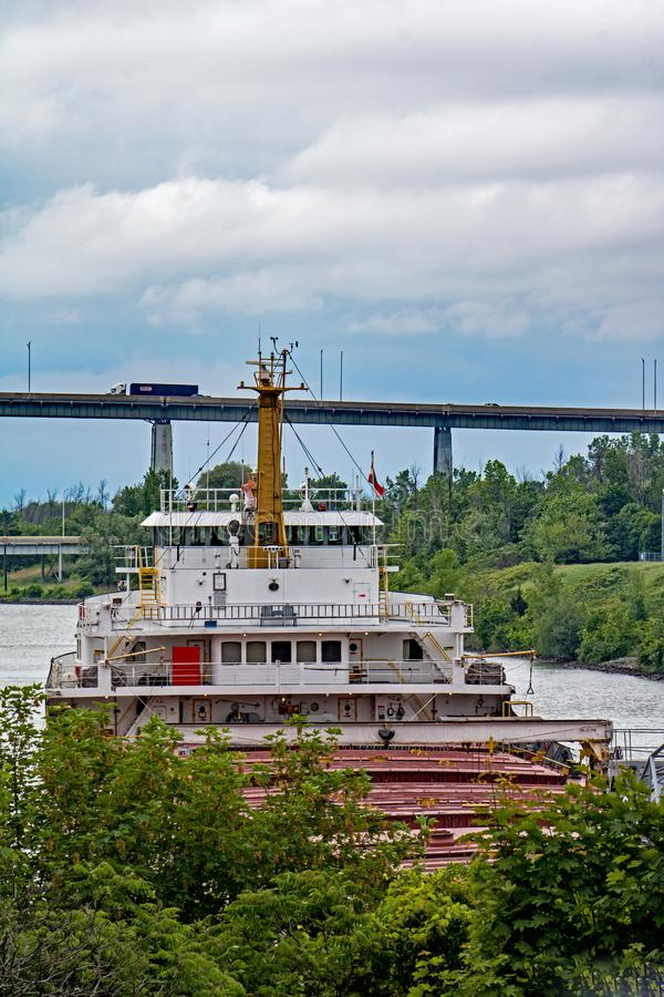 Great Lakes Freighter About To Go Under Highway Bridge. A great lakes freighter heads toward Lake Ontario after transiting the final lock in the Welland Canal royalty free stock photo