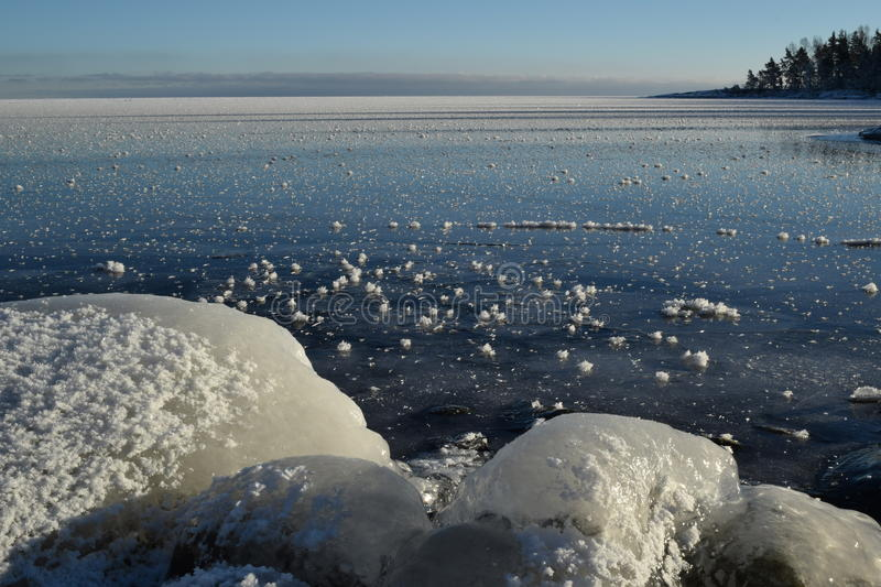 Great Lakes Ice-Covered Rocks Frozen Lake Superior. Chilly Winter day, clear blue sky and sun over frozen Lake Superior, ice-covered rocks and shiny blue ice stock photography