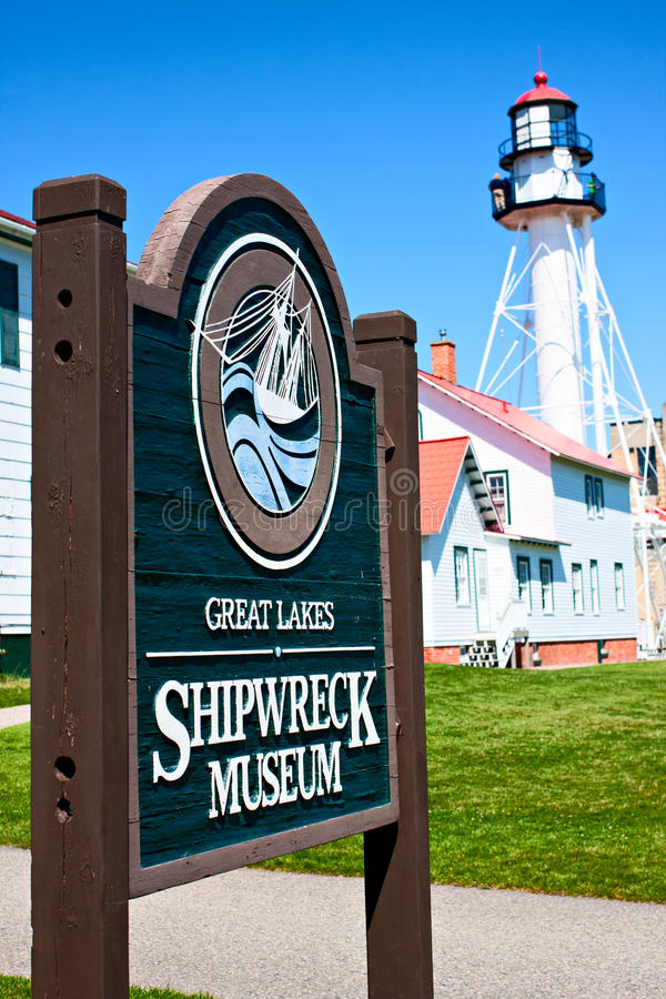 Great Lakes Shipwreck Museum and Whitefish Point Lighthouse. Whitefish Point Lighthouse behind the Great Lakes Shipwreck Museum sign royalty free stock photography