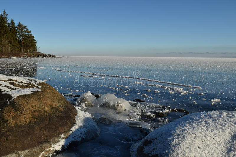 Great Lakes Winter Day Frozen Lake Superior Snow-Covered Rocks Copyspace. Early morning on a winter day, blue sky and sun over frozen Lake Superior, snow-covered royalty free stock photos