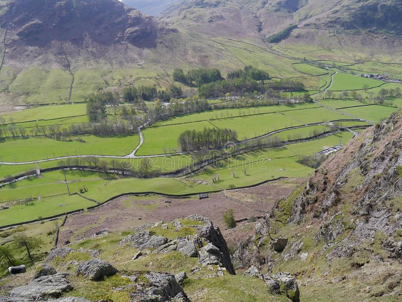 Great Langdale valley, Lake District. Looking down from a rocky hillside to verdant fields in Great Langdale valley with campsite area to the back stock images