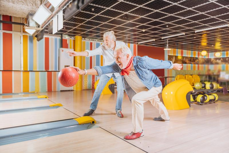 Cheerful nice elderly men having fun together. Great mood. Cheerful nice men having fun while playing bowling together stock photography