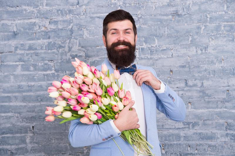In great mood. Greeting spring. March 8. Love. international holiday. Bearded man with wedding tulip bouquet. Womens day stock photography