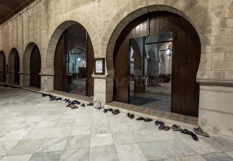 Great Mosque of Sousse in Tunisia. People Shoes in fron of entrance. Right before evening worship. Friday evening stock image