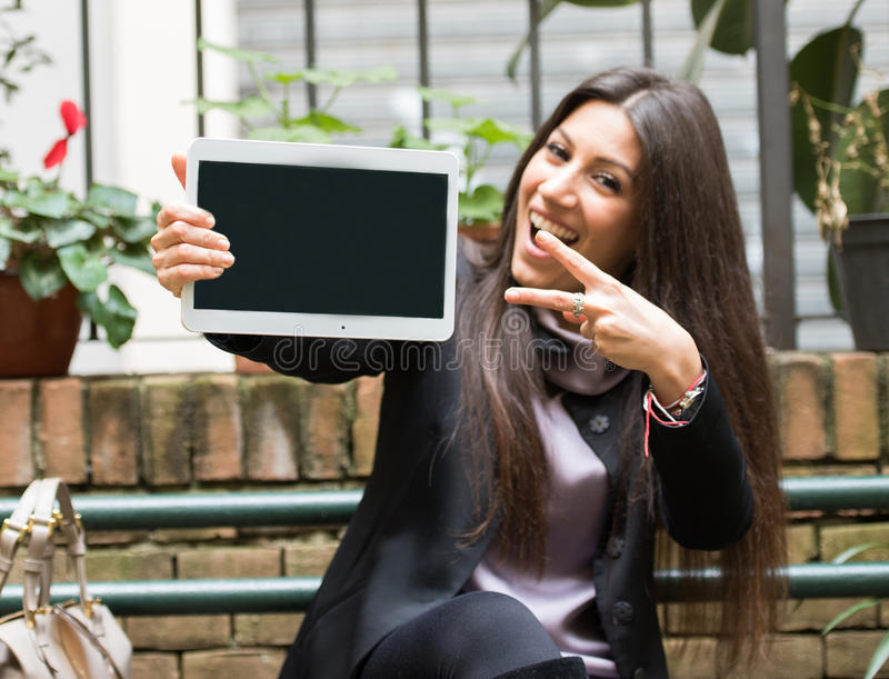 Great new deal. Beautiful young brunette woman dressed in a business casual work suit holding a white tablet with blank screen and making the peace sign. Amazing stock photos