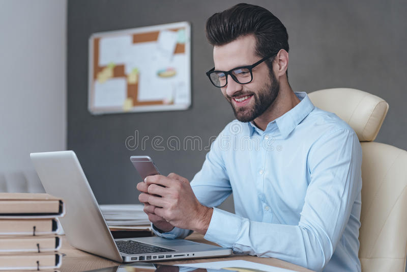 Great news. Handsome young man wearing glasses holding smart phone and looking at it with smile while sitting at his working place royalty free stock photo