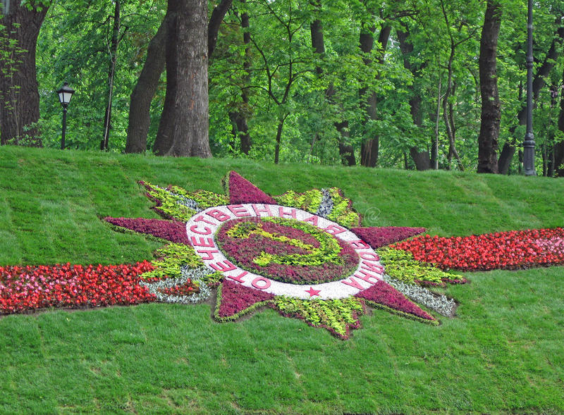 Great Patriotic War sign, Kiev, may 2010,. Great Patriotic War star sign from different colorful flowers on green grass lawn background near Mariyinsky park in stock photo