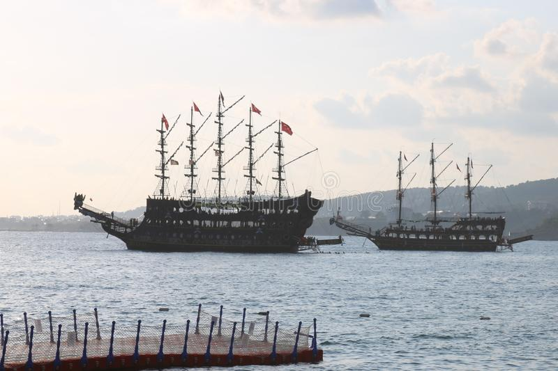 Great pirat ship in sea, Turkey. Sunset and old ship. The ancient pirate ship by the shore stock images