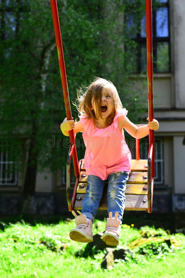 Great pleasure. romantic little girl on the swing, sweet dreams. Happy laughing child girl on swing. Small kid playing stock image