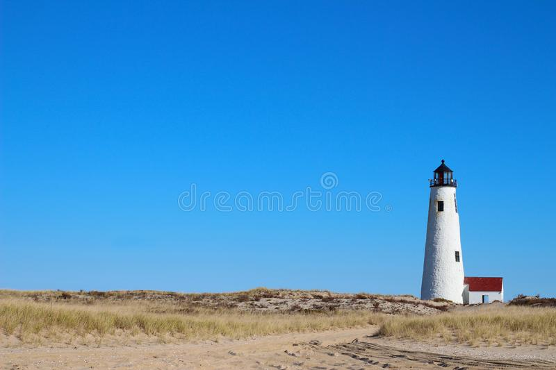 Great Point Light Lighthouse Nantucket Massachusetts MA with Blue Sky, Beach Grass and Dunes and Sand royalty free stock photos