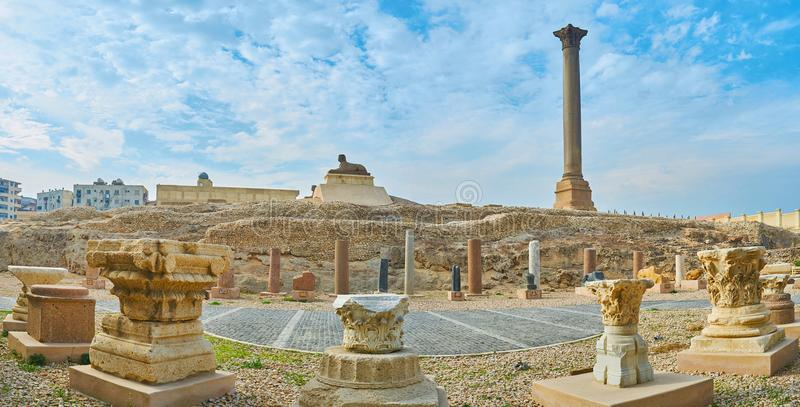 Panorama with Pompey`s Pillar and sphinx, Alexandria, Egypt. The great Pompey`s Pillar with sphinx statue in front of it and ruins of ancient Serapeum Temple on royalty free stock images