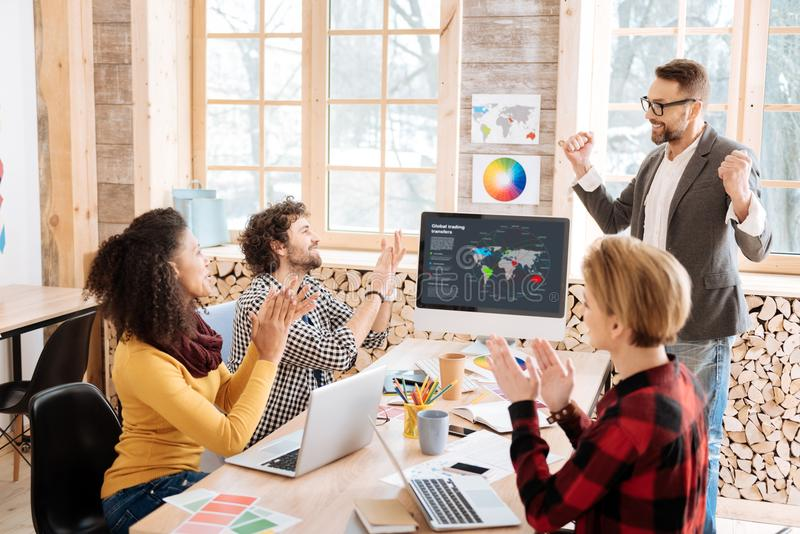 Happy employees clapping to their boss. Great results. Good-looking exuberant smiling and standing in front of his employees and they clapping to him royalty free stock images