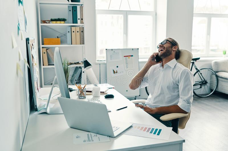Great results!. Good looking young man in shirt talking on the smart phone and smiling while sitting in the office stock image