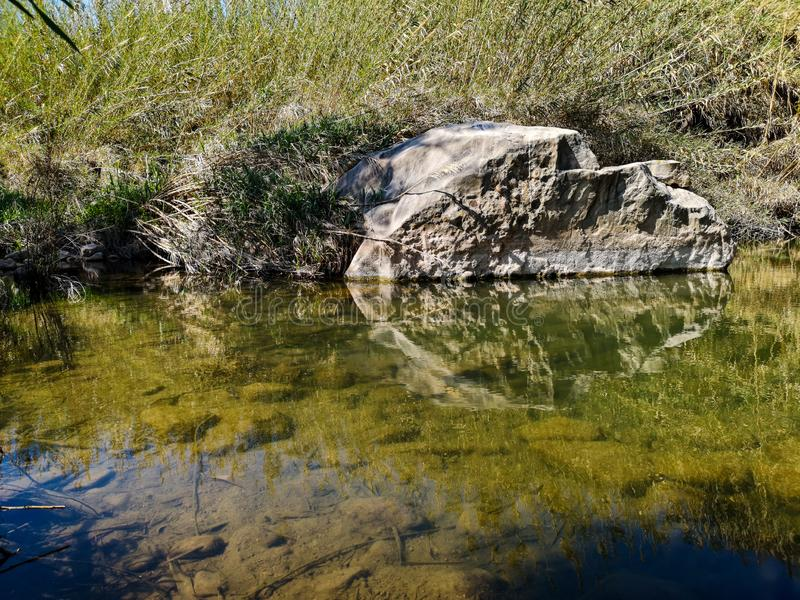 Great rock in river. Large rock reflected in the waters of the Palancia river scenery sky landscape blue natural reflection nature erosion shadow stillness earth stock photography