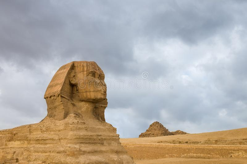 Great Sphinx profile wih pyramids on background in Giza, Egypt royalty free stock image