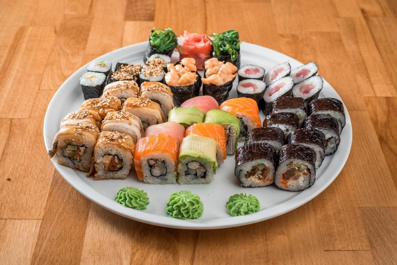 Great sushi set. Rolls with salmon, eel, avocado and tuna on a white plate. Japanese cuisine royalty free stock photos