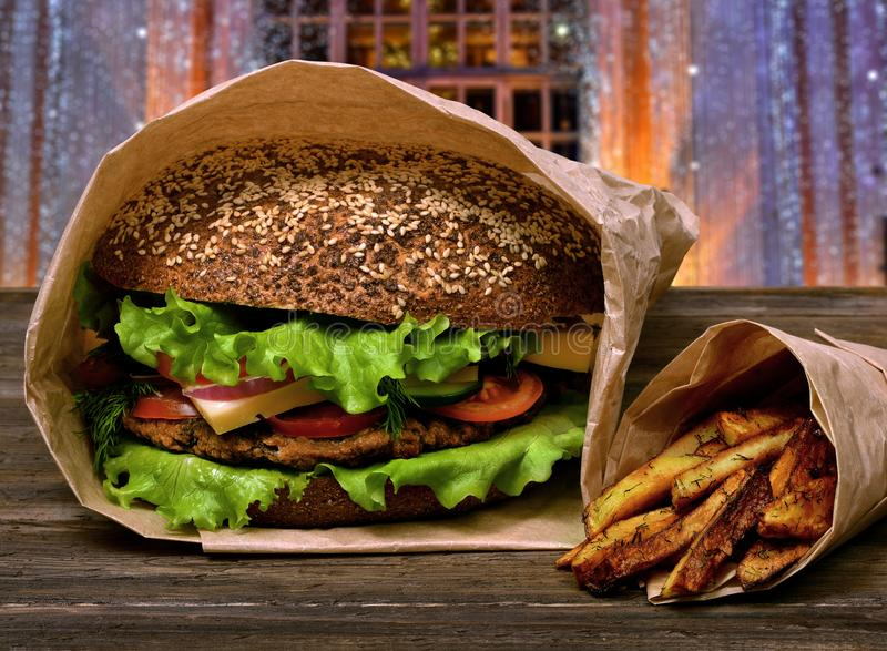 Great tasty hamburger and french fries on a wooden table stock photos
