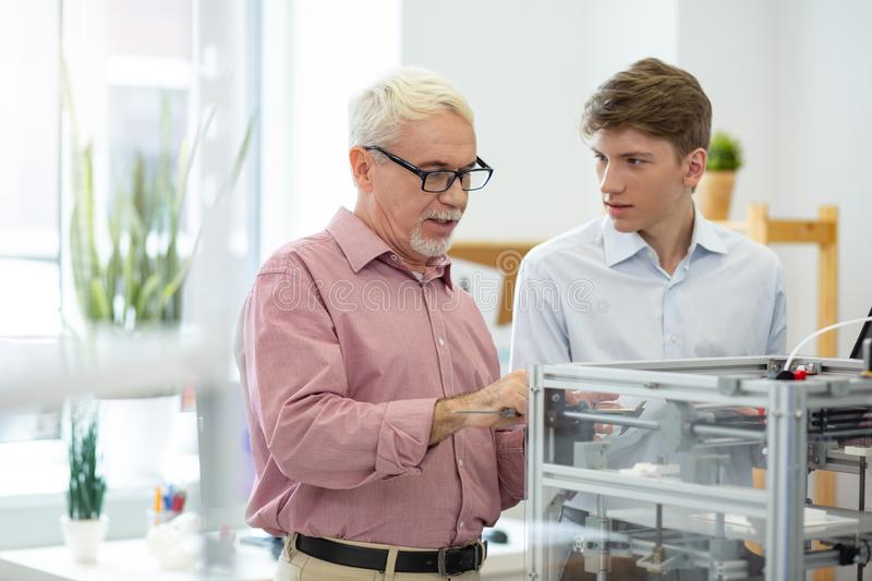 Senior engineer showing intern how to take measures with caliper. Great teacher. Pleasant senior engineer showing his intern how to take measures with caliper royalty free stock photos