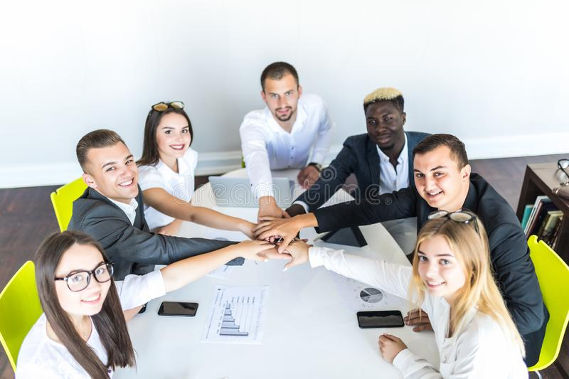 We are the great team. Group of happy business people holding hands together while sitting around the desk royalty free stock photo