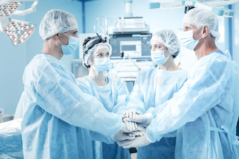 Positive nice surgeons holding hands together royalty free stock photography