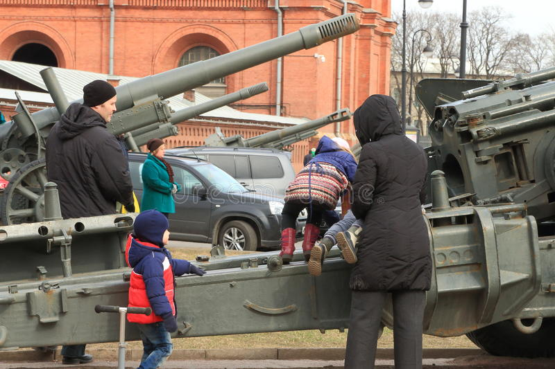 Great toy. Children play on the gun carriage under the supervision of their parents. Outside the Museum exposition. The Military-historical Museum of Artillery royalty free stock photo