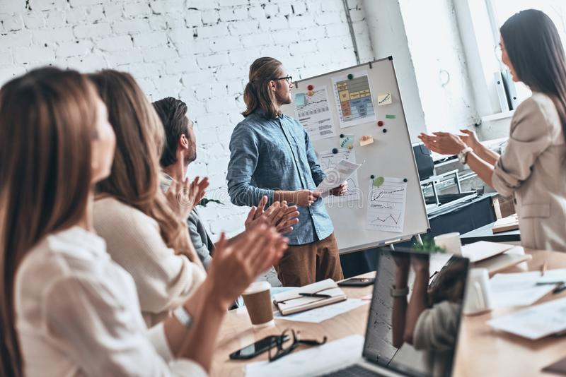 Great work. Group of business people clapping while standing in royalty free stock images