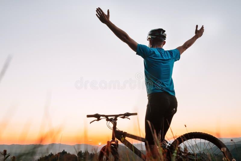 Greats велосипедиста человека заход солнца в горах стоковое фото