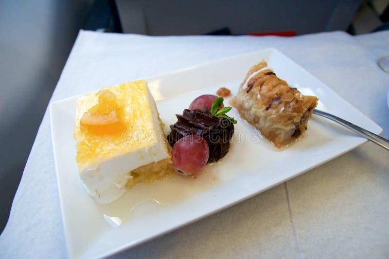 GRECIA - 15 de octubre de 2016: comida griega de la clase de negocios en un avión con el postre foto de archivo