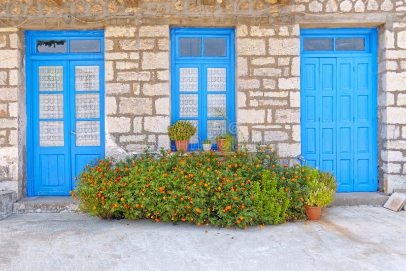 Grecia, flores de la maravilla delante de las puertas y de la ventana azules, fachada de la casa imagenes de archivo