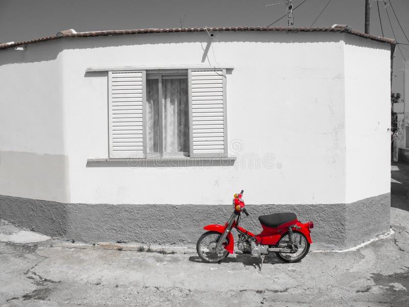 Grecia, Rodas, abril de 2019 Moto roja al lado de la casa blanca tradicional blanco y negro del pueblo imagenes de archivo