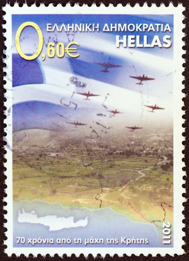 GRECJA - OKOŁO 2011: Znaczek drukujący w Grecja przedstawień grka samolotach nad Crete i fladze, około 2011 fotografia royalty free
