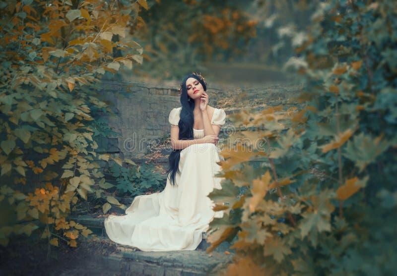 Grecka bogini siedzi na kamiennych krokach w jesień lesie, lekka skóra, biel długa elegancka suknia jak rzeźba, czerń zdjęcie royalty free
