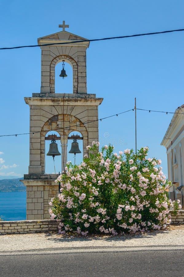 Grecka dzwonnica koło kościoła z dużym azalskim krzakiem przy drodze zdjęcie stock