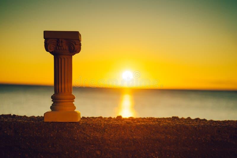 Grecka kolumna na brzeg i zmierzch nad morzem ukazujemy si? zdjęcie stock
