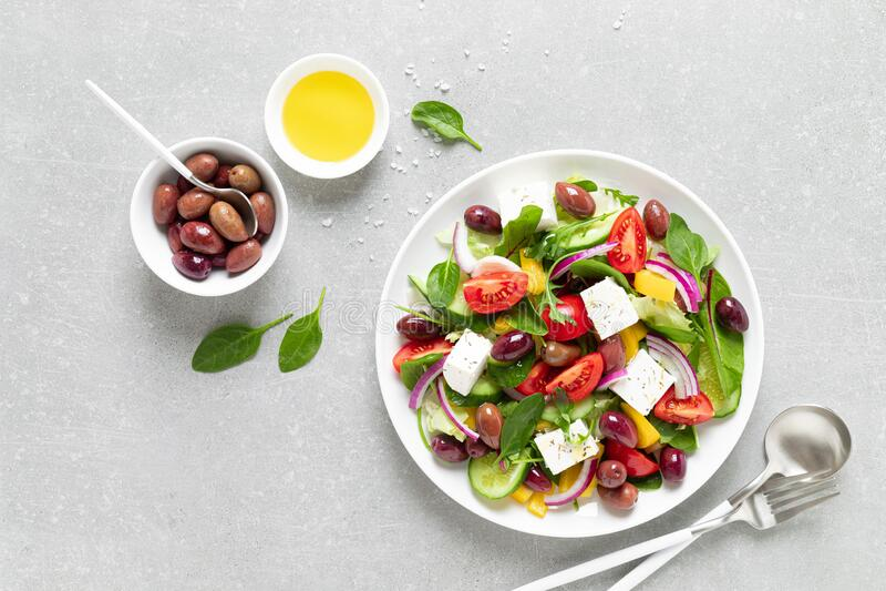 Grecka sałatka z zielonymi, oliwkami i fetą na białym talerzu obrazy royalty free