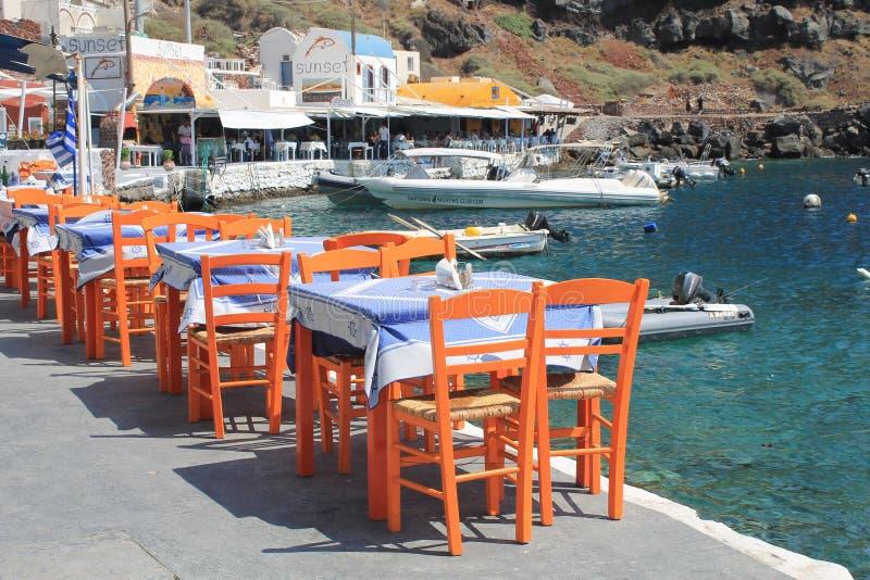 Grecka tawerna z pomarańczowymi drewnianymi krzesłami dennym wybrzeżem, Grecja, obrazy stock