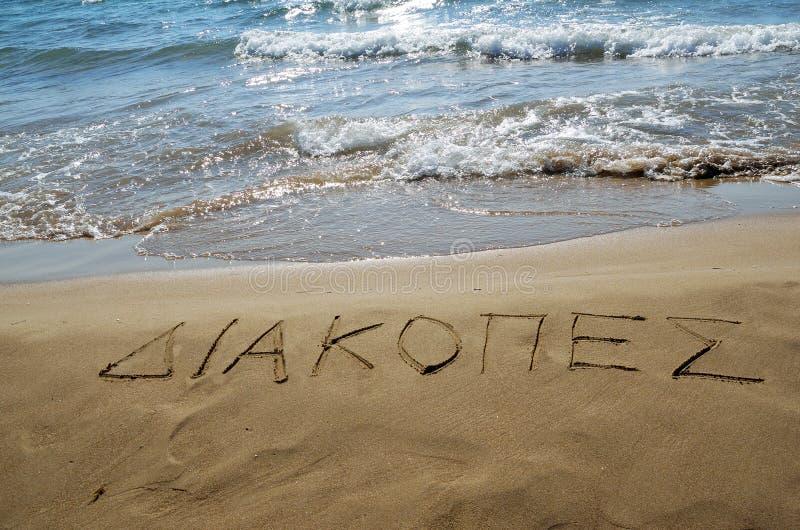 Grecki słowo 'Î'Î ¹ ακΠ¿ Ï€ÎÏ 'Â' pisać w piasku zdjęcia royalty free