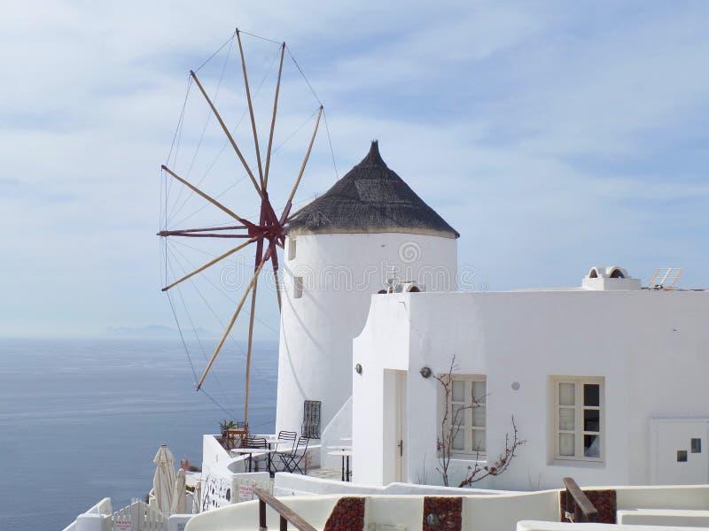 Grecki Tradycyjnego stylu wiatraczek i Biała willa przy Oia wioską na Santorini wyspie, Grecja obraz stock