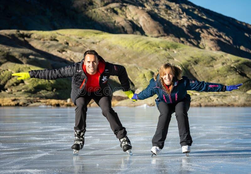Gredos,西班牙 12 1月2019 在一个可爱的晴朗的冬日期间,一个冻湖的夫妇滑冰的户外,西班牙 免版税库存图片