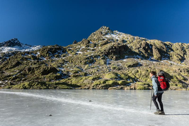 Gredos, Espagne 12-January-2019 Trekker de femme marchant au-dessus du beau lac de glace pendant un jour d'hiver ensoleillé vers  photo libre de droits