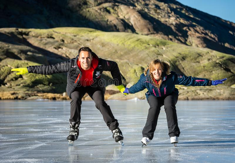 Gredos, Spain. 12-January-2019. Couple ice skating outdoors on a frozen lake during a lovely sunny winter day, Spain royalty free stock image