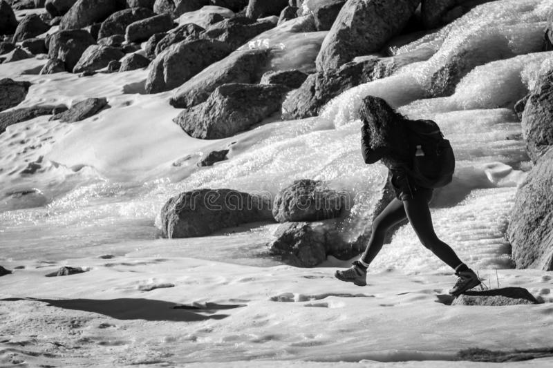 Gredos, Spain. 12-January-2019. Monochrome picture of woman trekker walking through ice during a winter sunny day royalty free stock photos