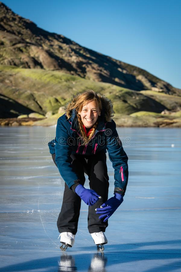 Gredos, Spain. 12-January-2019. Woman ice skating on a frozen lake during a lovely winter sunny day stock images